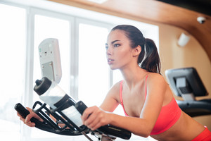 Beautiful serious young sportswoman training on bicycle in gym