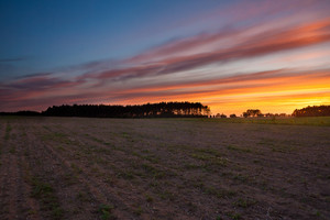 Beautiful sky after sunset over plowed field in springtime