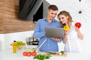 Beautiful smiling couple using laptop and making salad on the kitchen