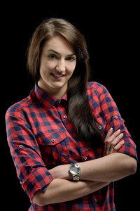 Beautiful smiling girl in checkered shirt posing on a black background