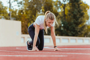 Beautiful sports woman standing in start position for run on outdoor stadium