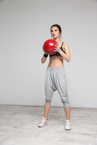 Beautiful sports woman working out with a medicine ball