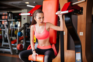 Beautiful strong young woman athlete exercising in gym