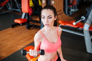 Beautiful strong young woman athlete training using dumbbells in gym