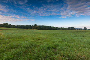 Beautiful sunrise over misty meadow. Cludy sky with many colors over morning meadow in summer.
