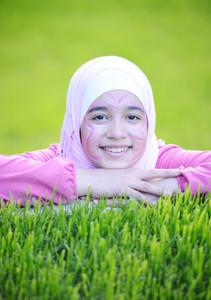 Beautiful teenage Arabic girl lying on green grass in nature