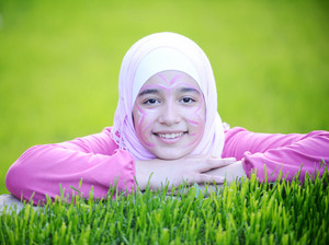 Beautiful teenage Arabic girl lying on green grass in nature