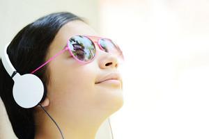 Beautiful teenage girl with sunglasses listening to music on headphones and enjoying