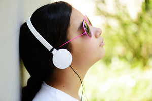 Beautiful teenage girl with sunglasses listening to music on headphones and enjoying