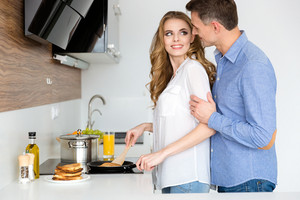 Beautiful wife making pancakes and flirting with her handsome huband on the kitchen