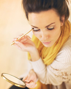 Beautiful woman applying eyeshadow while looking at the mirror