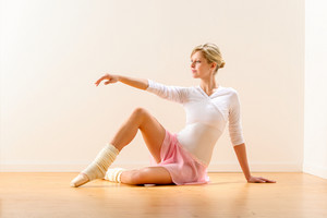 Beautiful woman dancer practicing ballet in studio ballerina arm raising