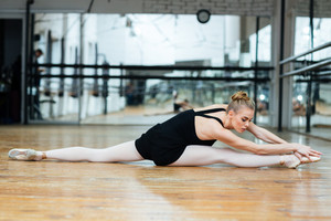 Beautiful woman doing stretching exercises on the floor in ballet class