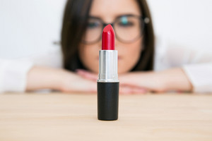 Beautiful woman looking on the lipstick. Focus on lipstick
