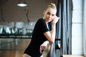 Beautiful woman resting in ballet class and looking away