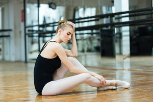 Beautiful woman resting on the floor in ballet class