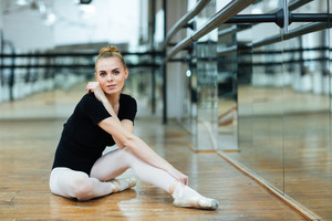 Beautiful woman sitting on the floor in ballet class and looking at camera