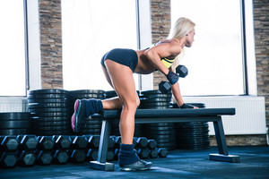 Beautiful woman workout with dumbbell on the bench in crossfit gym