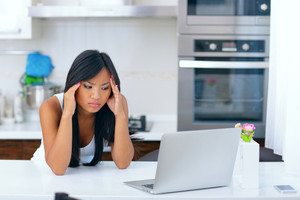 Beautiful young asian woman having a headache at home in front of her computer