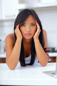 Beautiful young asian woman having a headache at home