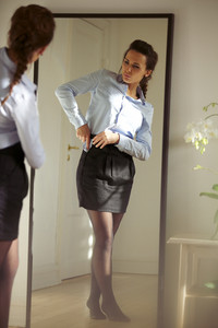 Beautiful young businesswoman fixing her skirt in front of mirror. Pretty caucasian female model getting dressed.