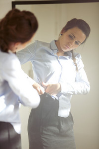 Beautiful young businesswoman wearing business attire in front of mirror. Young caucasian female model getting dressed at home.
