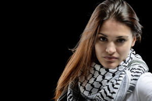 Beautiful young girl with palestinian scarf in front of dark background