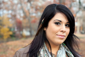 Beautiful young Hispanic woman wearing custom feather hair extensions in her black hair.