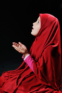 Beautiful young muslim girl praying on black background
