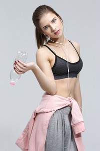 Beautiful young sporty woman standing with bottle of water