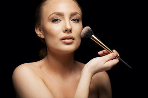 Beautiful young woman applying foundation on her face with a makeup brush isolated on black background. Attractive young caucasian model.