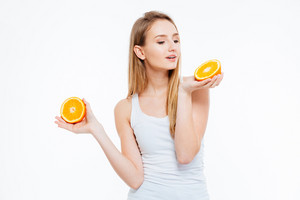 Beautiful young woman holding orange isolated on a white background