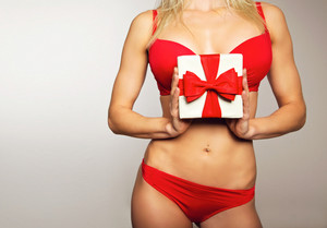 Beautiful young woman in red underwear holding a christmas gift