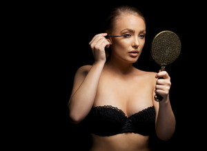 Beautiful young woman wearing black bra putting some mascara onto her eyelashes with make up brush. Sexy caucasian female model with mirror against black background.
