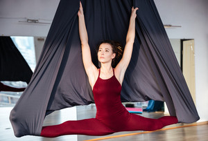Beautiul inspired young woman doing aerial yoga on black hammock in studio