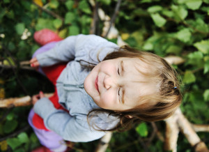 Beauty blond baby on tree leaves ground with closed eyes