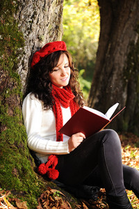 Beauty gorgeous autumn girl sitting in nature beside the tree and reading the book and studing