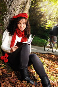 Beauty gorgeous autumn girl sitting in nature beside the tree and reading the book