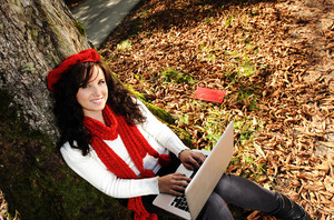 Beauty gorgeous autumn girl sitting in nature beside the tree and working on laptop