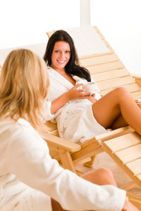 Beauty health luxury spa two women relax talking sitting sun-beds