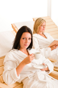 Beauty health spa treatment two women relax sun-beds coffee book