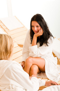 Beauty luxury spa room two women relax chatting on sun-beds