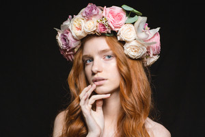 Beauty portrait of a charming redhead woman with wreath from flowers on head looking at camera over black background