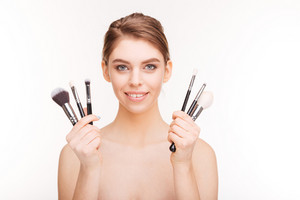 Beauty portrait of a happy woman holding makeup brushes  isolated on a white background
