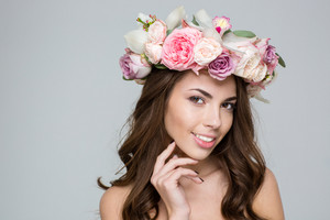Beauty portrait of a happy woman with wreath from flowers on head looking at camera over gray background