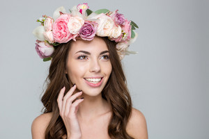Beauty portrait of a happy woman with wreath from flowers on head looking away over gray background