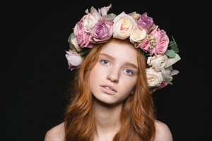 Beauty portrait of a pretty redhead woman with wreath from flowers on head looking at camera over black background