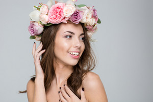 Beauty portrait of a pretty woman with wreath from flowers on head looking at camera over gray background