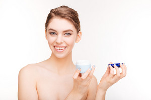 Beauty portrait of a smiling cute woman holding facial cream isolated on a white background