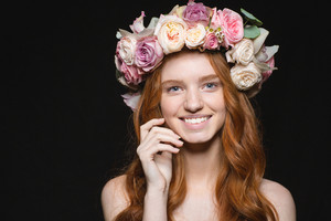 Beauty portrait of a smiling redhead woman with wreath from flowers on head standing over black background